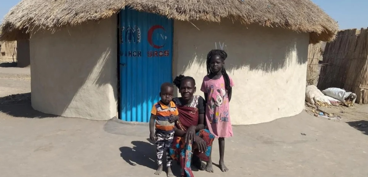 Aban, 44, with two of her children in front of their durable shelter in Al Jameya camp in White Nile State, Sudan.