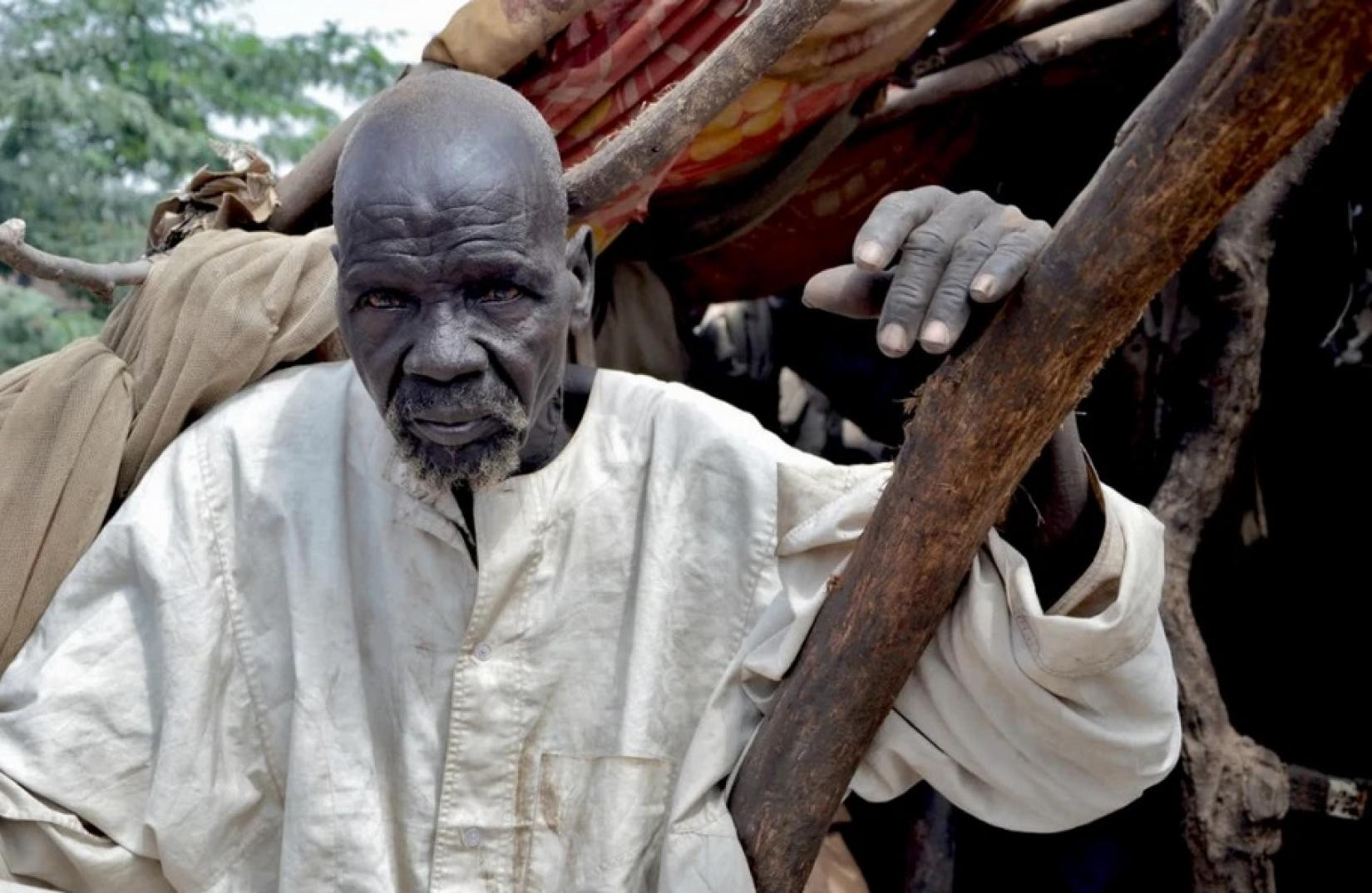 South Sudanese refugee, Bak, 80, sits in his shelter that was damaged by massive flooding in Sharq Al-Nile, Sudan.   © UNHCR/Roland Schönbauer