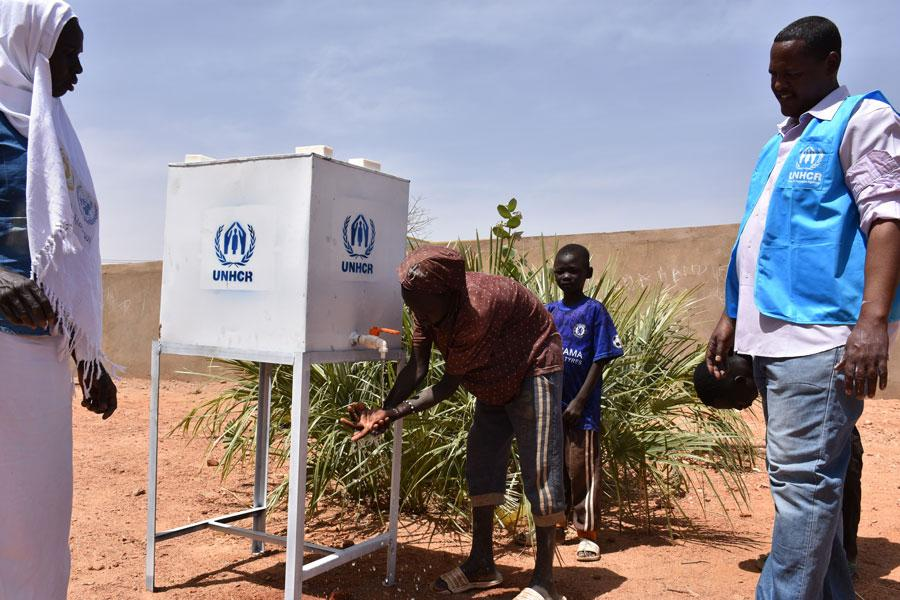 South Sudanese refugees washing their hands at a UNHCR facility during a registration exercise in South Darfur. Prior to the registration, UNHCR conducted a sensitization session about COVID-19, which included handwashing techniques.