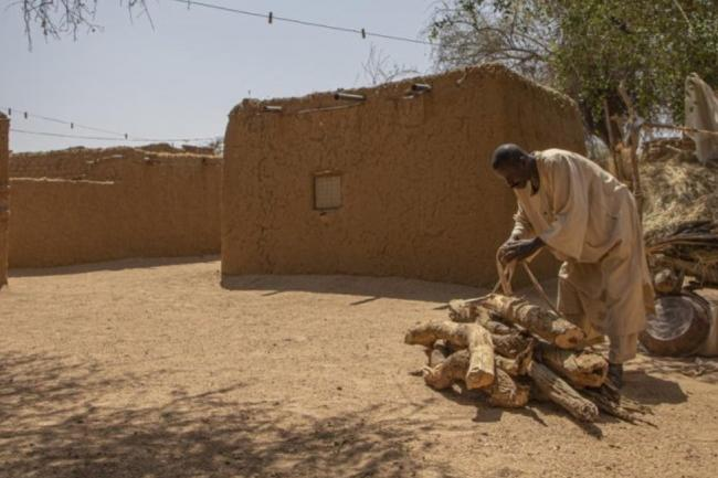 Ahmed Ishag Babiker, 54, piles up firewood in his compound in Kabkabiya in North Darfur, Sudan. He and his family were displaced when armed militias attacked his village in Wadi Bare in 2004.  © UNHCR/Will Swanson