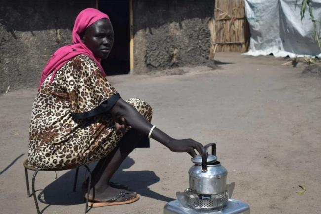 Alisa, 35, cooks on her new ethanol stove outside her compound in White Nile state, Sudan.